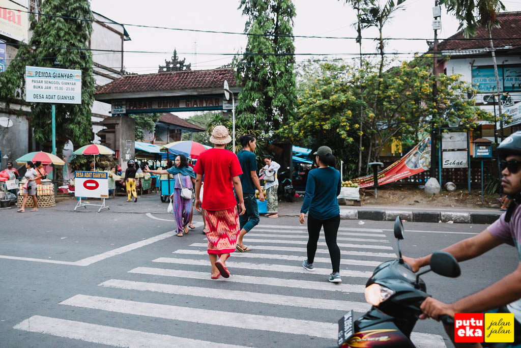 Putu Eka Jalan Jalan sedang menyebrang jalan menuju Pasar Senggol Gianyar