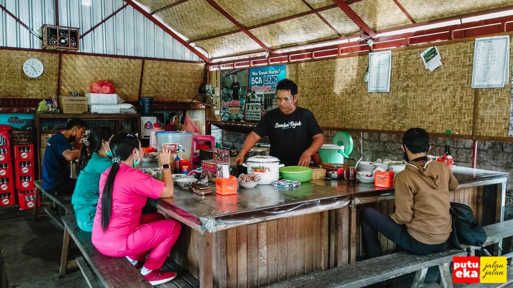Penjual sedang menyiapkan menu dengan menggunakan face shield