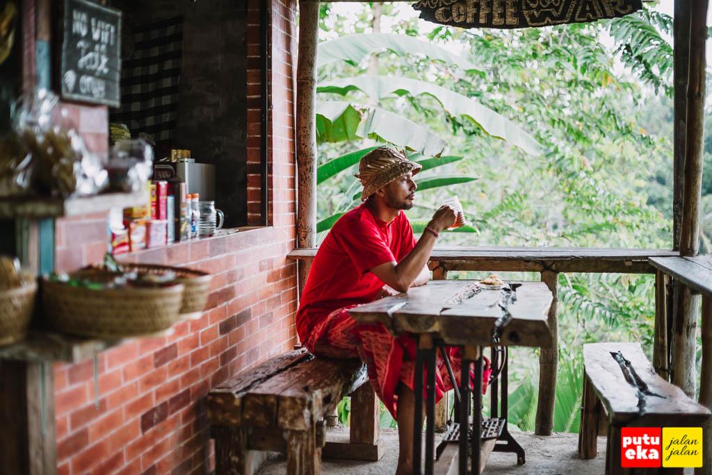 Putu Eka Jalan Jalan sedang duduk sambil minum teh