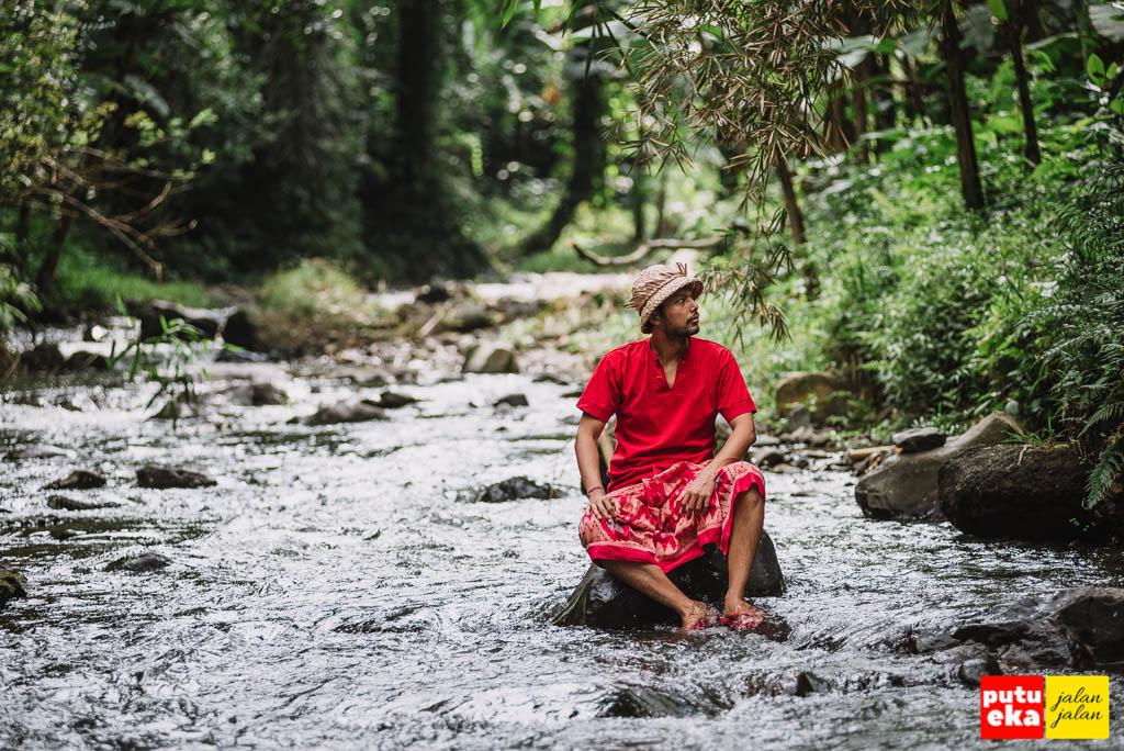 Duduk di atas batu ditengah aliran sungai