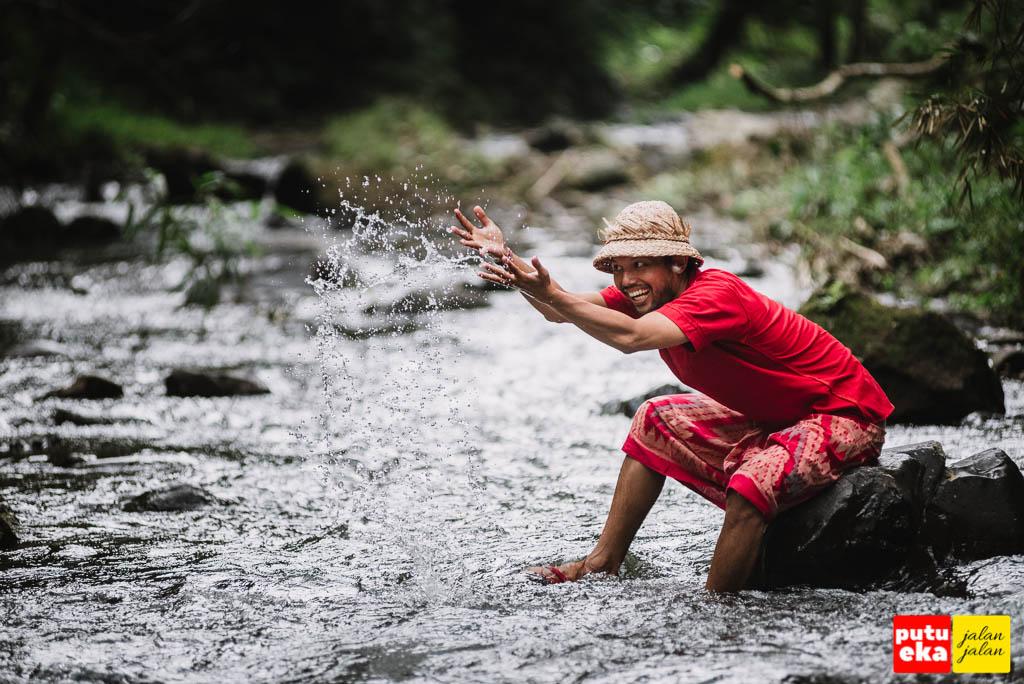 Bermain air ditengah sungai kecil didepan air terjun