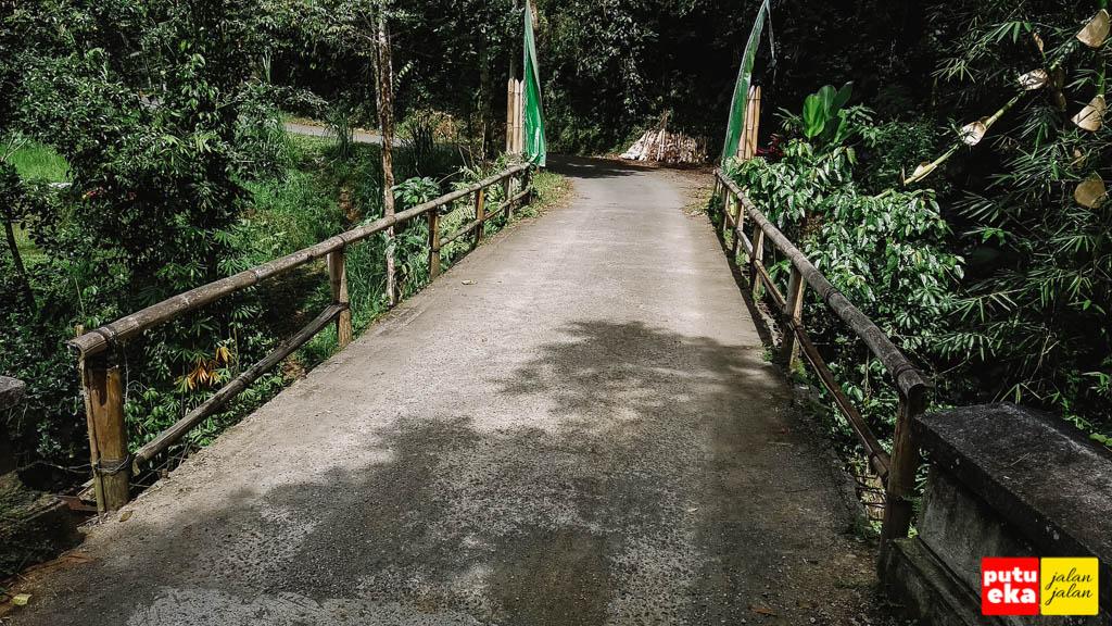Jembatan dengan pagar bambu didekat air terjun