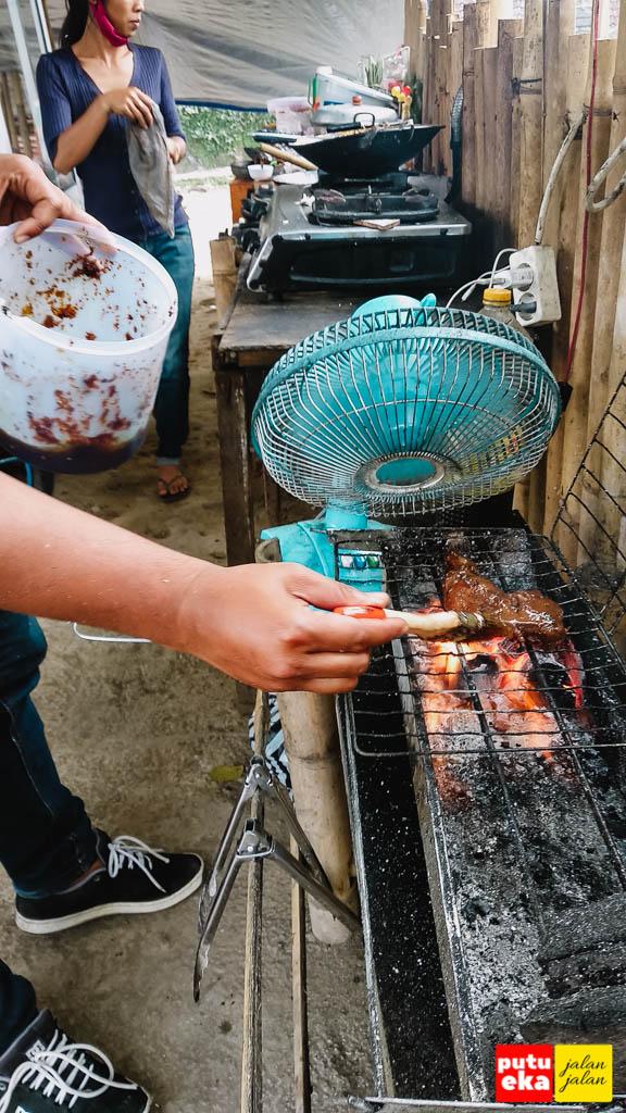 Ayam bakar enak sedang dioles bumbu rahasia ketika dibakar