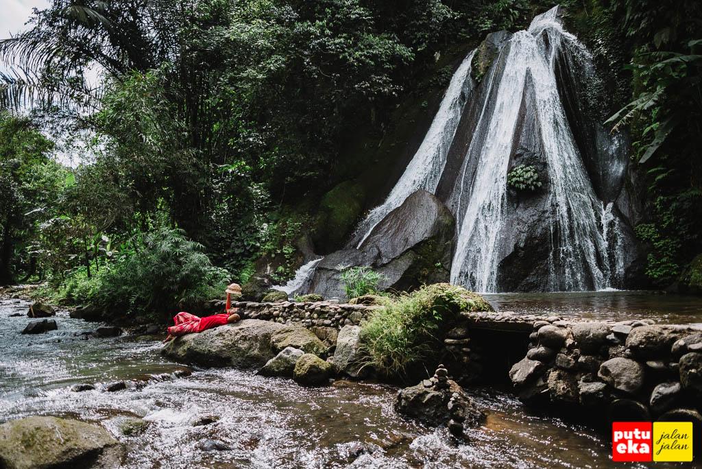 Berbaring santai diatas batu air terjun Campuhan Antapan