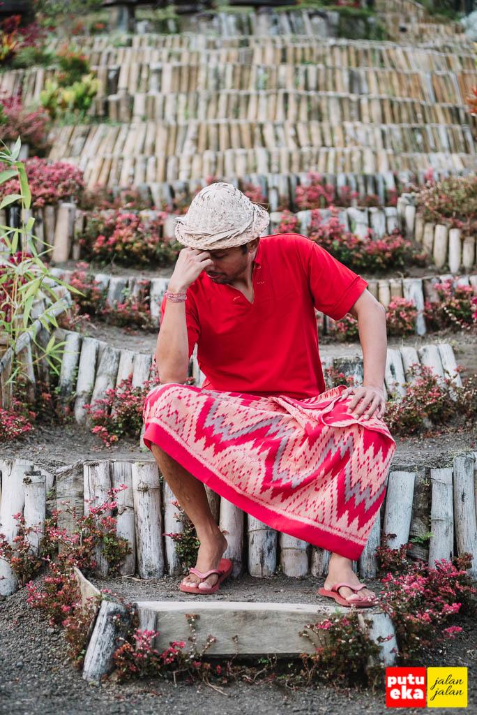 Putu Eka Jalan Jalan duduk diantara undagan yang diperkuat dengan batang bambu