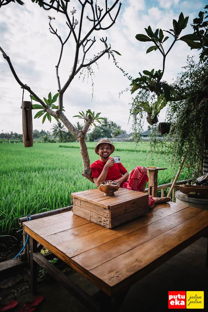 Duduk santai sambil bersandar ke pohon Kamboja