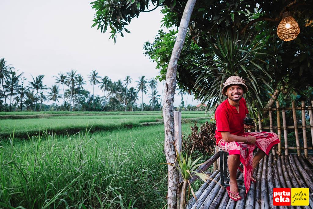 Putu Eka Jalan Jalan sedang duduk di Dek Bambu Kopi Lais Denbantas