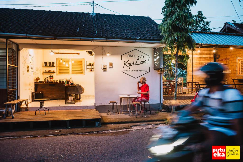 Putu Eka Jalan Jalan menyeruput kopi di tempat duduk tepi jalan