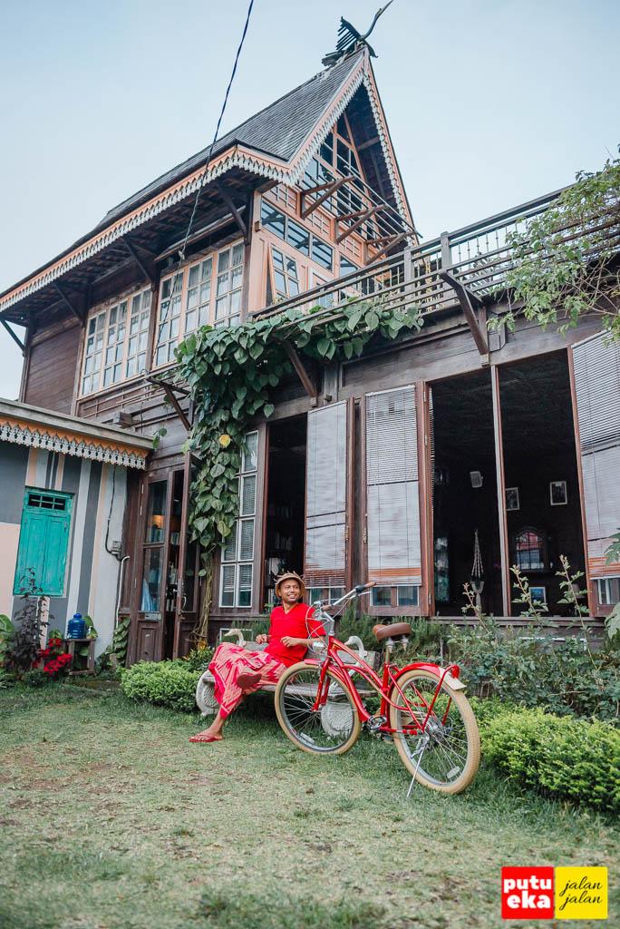 Bangunan Casa Tua tampak dari halaman dengan Putu Eka Jalan Jalan sedang duduk didepannya