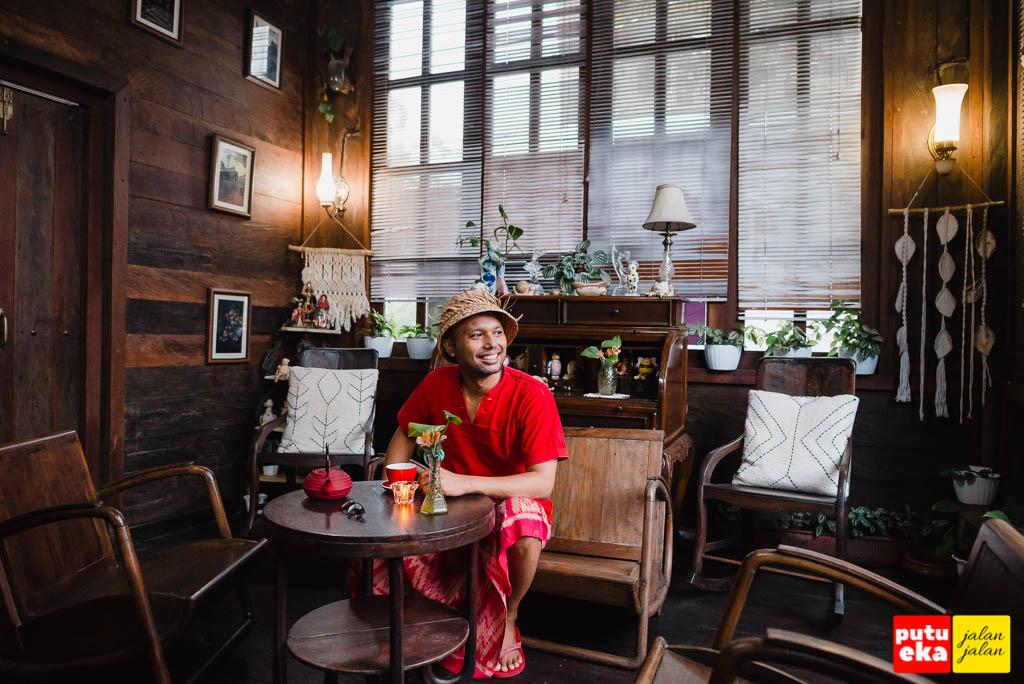 Putu Eka Jalan Jalan duduk di tempat duduk kayu zaman dahulu