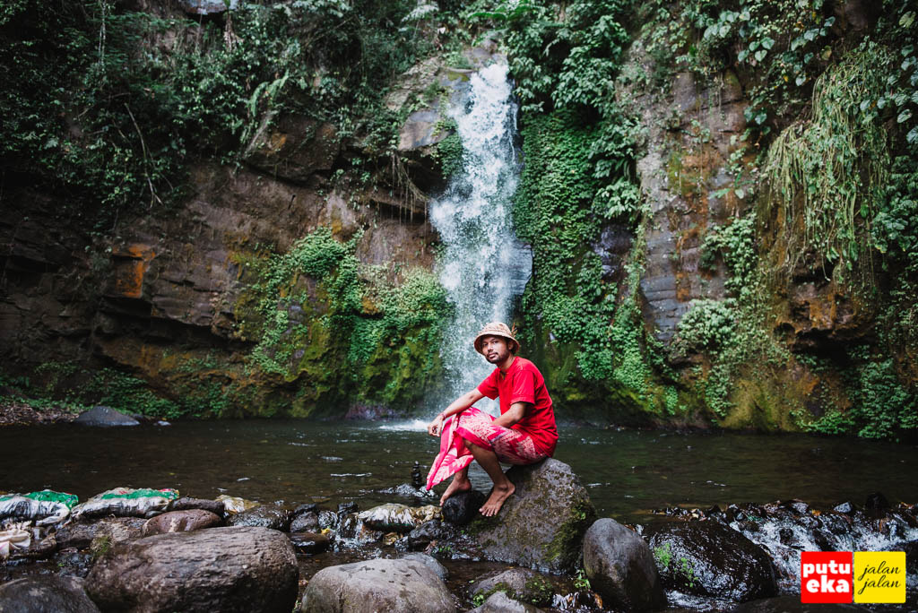 Putu Eka Jalan Jalan duduk diatas batu di depan Air Terjun Gong Batu Lantang