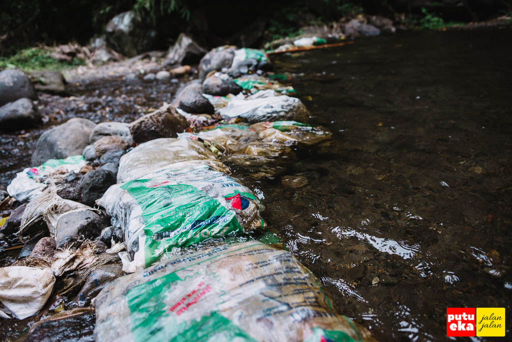 Batu-batu kecil dimasukkan ke dalam karung plastik untuk membendung air
