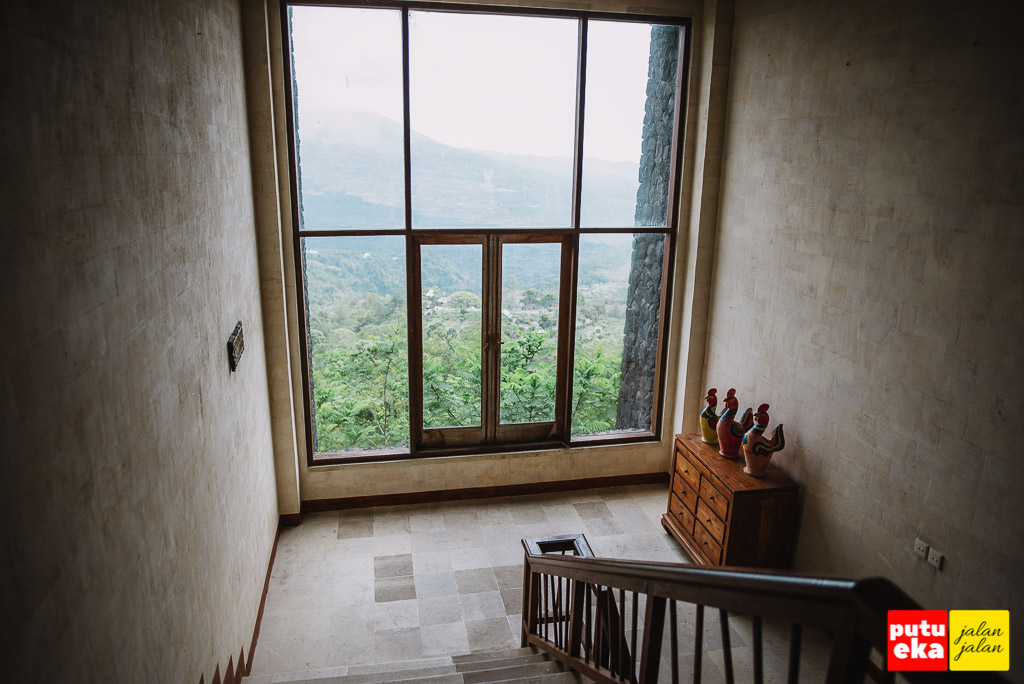 Tangga turun dengan kaca yang luas mengarah ke Gunung Batur